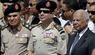 ** FILE ** In this Friday, Sept. 20, 2013, file photo, Egypt's Defense Minister Gen. Abdel-Fattah el-Sissi, center, Egyptian Prime Minister Hazem el-Beblawi, right, and army's Chief of Staff Lt. Gen. Sedki Sobhi, left, attend the funeral of Giza Police Gen. Nabil Farrag in Cairo, Egypt. (AP Photo/Hassan Ammar, File)