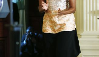 First lady Michelle Obama arrives on stage  in the East Room at the White House in Washington, Tuesday, Feb. 25, 2014, to announce proposed guidelines for local school wellness policies during an event. (AP Photo/Charles Dharapak)