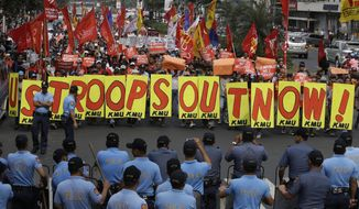 Riot police prepare to prevent protesters from marching closer to U.S. Embassy Tuesday, Feb. 25, 2014 in Manila, Philippines, against the forthcoming visit of U.S. President Barack Obama. The protesters were also calling for the pullout of U.S. troops in the country under the Visiting Forces Agreement or VFA. (AP Photo/Bullit Marquez)