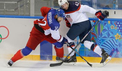 Czech Republic defenseman Michal Rozsival and USA forward David Backes battle for control of the puck during the second period of men's quarterfinal hockey game in Shayba Arena at the 2014 Winter Olympics, Wednesday, Feb. 19, 2014, in Sochi, Russia. (AP Photo/Matt Slocum)
