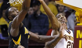 Minnesota guard Austin Hollins (20), Minnesota guard Malik Smith (30) and Iowa center Gabriel Olaseni, top, left, vie for a rebound during the second half of an NCAA college basketball game in Minneapolis, Tuesday, Feb. 25, 2014. Hollins had a career and game-high 27 points as Minnesota won 95-89. (AP Photo/Ann Heisenfelt)