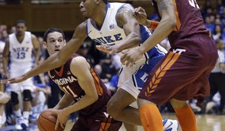 Virginia Tech's Devin Wilson (11) looks to pass to Jarell Eddie (31) as Duke's Rodney Hood defends during the first half of an NCAA college basketball game in Durham, N.C., Tuesday, Feb. 25, 2014. (AP Photo/Gerry Broome)