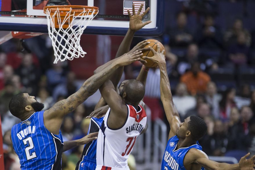 Washington Wizards forward Chris Singleton, drives to the basket against Orlando Magic forward Kyle O'Quinn, left, forward Andrew Nicholson, center, and forward Maurice Harkless during the first half of an NBA basketball game, Tuesday, Feb. 25, 2014, in Washington. (AP Photo/ Evan Vucci)