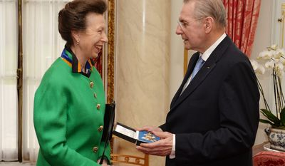 Britain's Princess Anne presents former International Olympic Committee (IOC) President Jacques Rogge with the insignia of a Knight Commander, Order of Saint Michael and Saint George, during a ceremony at Buckingham Palace in central London, Tuesday Feb. 25, 2014. (AP Photo/John Stillwell, Pool)