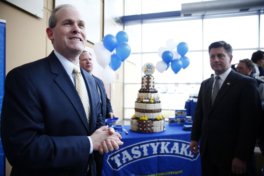Tastykake President Paul Ridder, left, accompanied by Pennsylvania Lt. Gov. Jim Cawley, invites attendees to have birthday cake, as Tastykake marks its 100th anniversary Tuesday, Feb. 25, 2014, in Philadelphia. Tastykake made 100 cakes on its first day of business in 1914. Now, it produces nearly 5 million cakes, doughnuts, cookies and pies each day. (AP Photo/Matt Rourke)