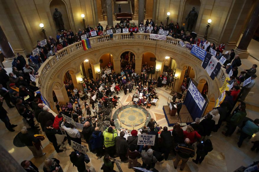 Demonstrators rally at the state Capitol, calling for lawmakers to raise the minimum wage, as the 2014 Minnesota Legislature convened, Tuesday, , Feb. 25, 2014, in St. Paul, Minn. (AP Photo/Jim Mone)