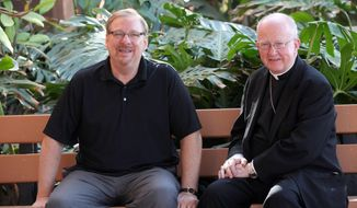 This Monday, Feb. 24, 2014 photo, Saddleback Church founder and senior pastor, Rick Warren, left, and Bishop of the Roman Catholic Diocese of Orange, Kevin William Vann, right, pose for a photo at the Saddleback Church in Lake Forest, Calif. Warren will partner with the Roman Catholic Church and the National Alliance for Mental Illness next month for the first event of what they hope will be a sustained project to get faith leaders more involved with mental health issues and advocacy. (AP Photo/Nick Ut )