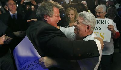 Revere, Mass. Mayor Dan Rizzo, left, is hugged by Kenneth Haggar at Suffolk Downs in Revere on Tuesday, Feb. 25, 2014 as supporters celebrate the passage of a referendum allowing the Mohegan Sun to move forward with its $1.3 billion proposal in Revere and compete with Wynn Resorts for the sole eastern Massachusetts resort casino. (AP Photo/Elise Amendola)