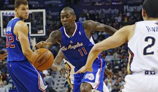 Los Angeles Clippers shooting guard Jamal Crawford (11) drives to the basket between New Orleans Pelicans shooting guard Austin Rivers (25) and Los Angeles Clippers power forward Blake Griffin (32) in the first half of an NBA basketball in New Orleans, Monday, Feb. 24, 2014. The Clippers defeated the Pelicans 123-110. (AP Photo/Bill Haber)