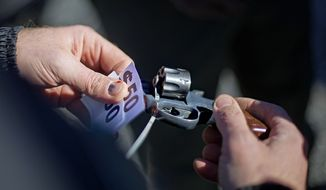 In this file photo, a police officer inspects a revolver turned in to exchange for money during a gun buyback in Atlanta on Jan. 16, 2014. Lawmakers in the North Dakota House of Representatives are considering a bill that would forbid the state's law enforcement agencies from conducting gun-buyback programs. (Associated Press)