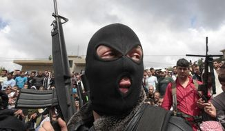 ** FILE ** A masked Lebanese Sunni gunman holds up his weapon in Akkar, north Lebanon. (AP Photo/Hussein Malla, File)