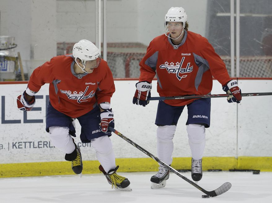 Washington Capitals captain Alex Ovechkin, left, and center Nicklas Backstrom work out  during a Capitals hockey practice, Tuesday, Feb. 25, 2014, at Kettler Capitals Iceplex in Arlington, Va. Ovechkin's father had heart surgery, and Backstrom missed the gold medal game because of a failed doping test. Both players are back from an eventful Olympics. (AP Photo/Carolyn Kaster)