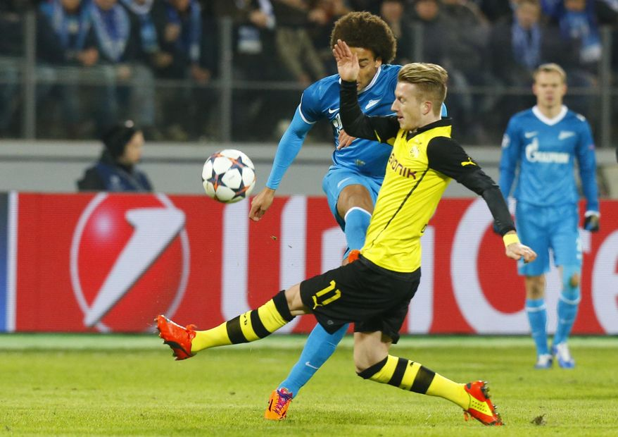 Borussia's Marco Reus blocks Zenit's Axel Witsel, right, from making a kick during the Champions League soccer match between Zenit St.Petersburg and  Borussia Dortmund at Petrovsky stadium in St.Petersburg, Russia, on Tuesday, Feb. 25, 2014. (AP Photo/Dmitry Lovetsky)
