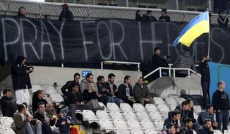 "Fans of Dynamo Kiev hold a banner that reads ""Pray for heroes"" in honor of victims of violent clashes in the Ukrainian capital, before the start of their Europa League round of 32 first leg match at GSP stadium in Nicosia, Cyprus, Thursday, Feb. 20, 2014. UEFA has moved the Dynamo Kiev vs. Valencia Europa League round of 32 opener to Cyprus, after anti-government clashes in the Ukrainian capital left at least 50 people dead and hundreds injured. (AP Photo/Petros Karadjias)"