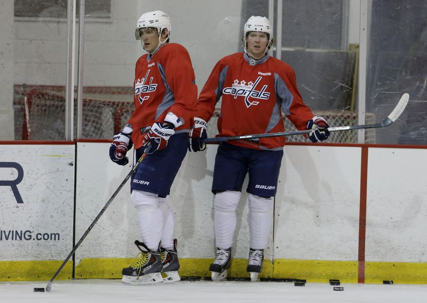 Washington Capitals captain Alex Ovechkin, left, and center Nicklas Backstrom pause during a Capitals hockey practice, Tuesday, Feb. 25, 2014, at Kettler Capitals Iceplex in Arlington, Va. Ovechkin's father had heart surgery, and Backstrom missed the gold medal game because of a failed doping test. Both players are back from an eventful Olympics. (AP Photo/Carolyn Kaster)