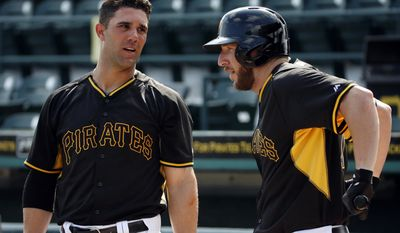 Pittsburgh Pirates' Brent Morel, right, talks with Andrew Lambo as he warms up before taking batting practice before the team's annual spring training Black and Gold intra-squad baseball game in Bradenton, Fla., Tuesday, Feb. 25, 2014. The Pirates will start Grapefruit League play Wednesday against the New York Yankees in Bradenton. Morel, acquired Monday from the Toronto Blue Jays, did not play in the game. (AP Photo/Gene J. Puskar)
