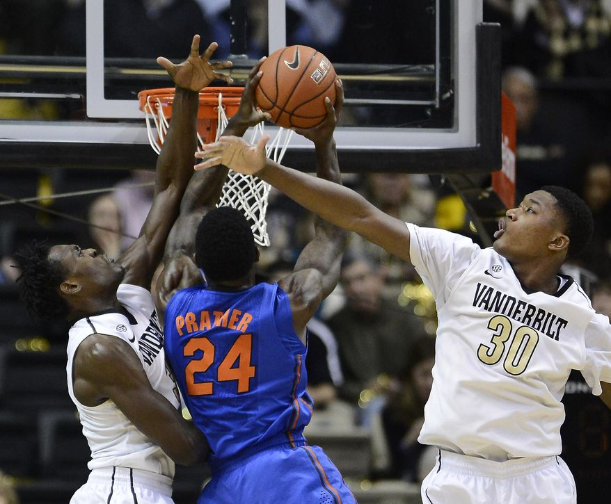 Florida forward Casey Prather (24) drives to the basket past Vanderbilt forward James Siakam, left, and forward Damian Jones (30) in the first half of an NCAA college basketball game on Tuesday, Feb. 25, 2014, in Nashville, Tenn.  (AP Photo/Mark Zaleski)