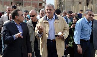 In this Nov. 24, 2013 photo, Ibrahim Mehlib, center, tours a government housing project in Ismailiya, Egypt. Egypt's interim president has chosen as prime minister a construction magnate from the era of ousted autocrat Hosni Mubarak. Adly Mansour on Tuesday, Feb. 25, 2014 named Mehlib, who had for more than a decade led Egypt's biggest construction company, Arab Contractors, to replace Hazem el-Beblawi, who resigned on Monday.(AP Photo/Khaled Kandil)