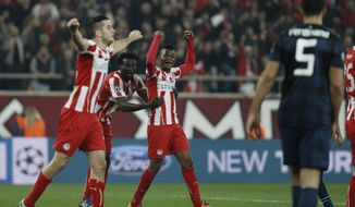 Olympiakos' players celebrate after the end of a Champions League, round of 16, first leg soccer match  against  Manchester Unitedat Georgios Karaiskakis stadium, in Piraeus port, near Athens, on Tuesday, Feb. 25, 2014. (AP Photo/Petros Giannakouris)