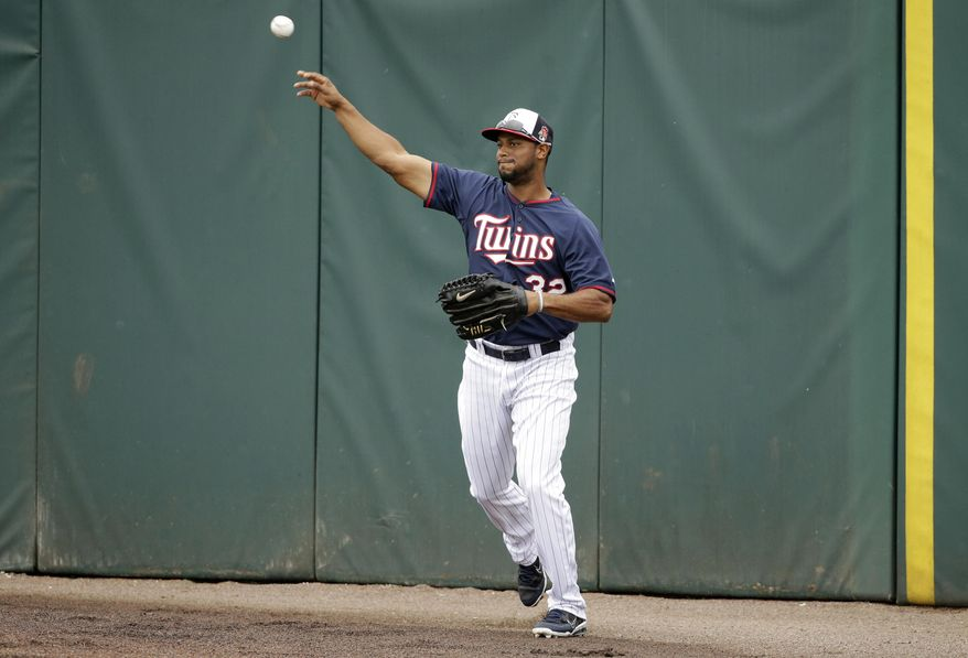 Minnesota Twins center fielder Aaron Hicks  fields the ball during spring training baseball practice Tuesday, Feb. 25, 2014, in Fort Myers, Fla. (AP Photo/Steven Senne)