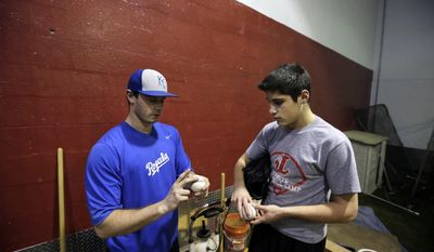 In this Feb. 24, 2014 photo, Kansas City Royals minor league pitcher,  John Walter, left, of Haddonfield, N.J., demonstrates a pitch as he instructs Steve Cocotoni, 15, at Power Train Sports Institute's AFC Baseball & Softball Academy in Cherry Hill, N.J.  (AP Photo/Mel Evans)