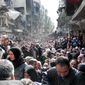 Residents of the besieged Palestinian camp of Yarmouk line up to receive food supplies in Damascus. A United Nations official is calling on warring sides in Syria to allow aid workers to resume distribution of food and medicine in the capital. (United Nations Relief and Works Agency via associated press)