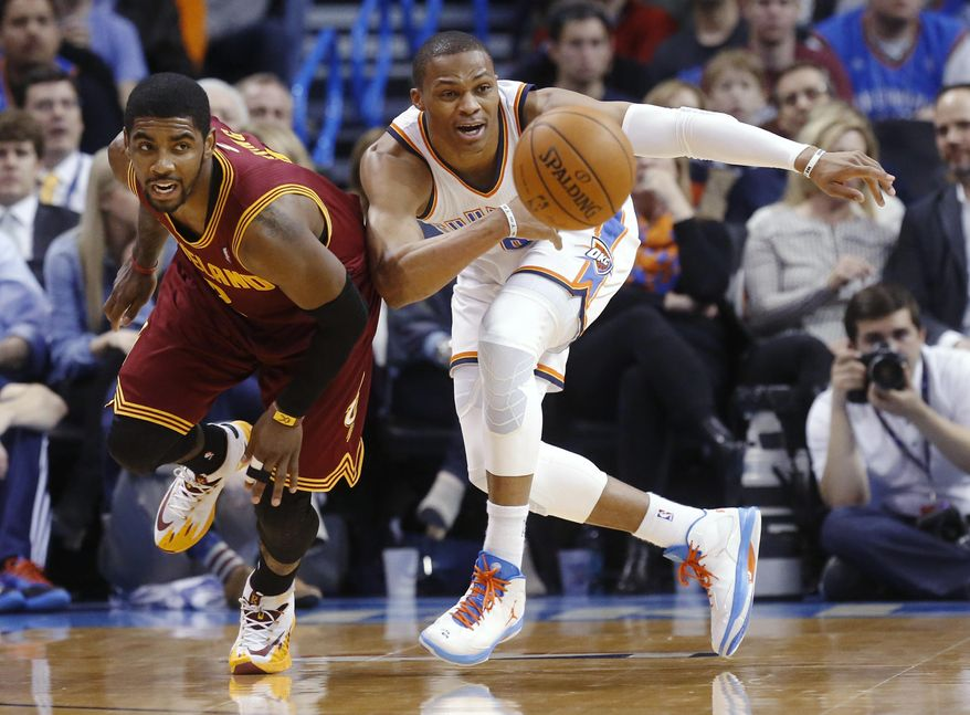 Cleveland Cavaliers guard Kyrie Irving, left, and Oklahoma City Thunder guard Russell Westbrook watch the ball during the second quarter of an NBA basketball game in Oklahoma City, Wednesday, Feb. 26, 2014. (AP Photo/Sue Ogrocki)