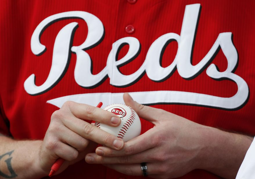Justin King, of Jerome, Idaho, waits for player autographs before an exhibition baseball game between the Cincinnati Reds and the Cleveland Indians in Goodyear, Ariz., Wednesday, Feb. 26, 2014. (AP Photo/Paul Sancya)