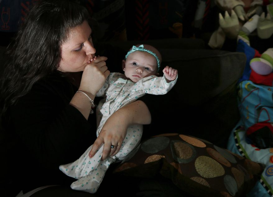 Jennifer Fontaine kisses her baby daughter, Morgan, at her parents' home in Methuen, Mass. on Tuesday, Feb. 25, 2014. After Fontaine's standard prenatal screening suggested her fetus might have Edwards syndrome, a doctor suggested a fetal DNA test, which suggested her fetus was fine. A simple test that looks for fetal DNA in a pregnant woman's blood is far more accurate at detecting or ruling out Down syndrome and other common chromosome disorders than other screening methods used now, a major study finds. (AP Photo/Elise Amendola)