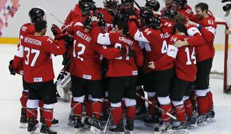 Canada goaltender Carey Price is swarmed by teammates as they celebrate after the men's gold medal ice hockey game against Sweden at the 2014 Winter Olympics, Sunday, Feb. 23, 2014, in Sochi, Russia. Canada won 3-0 to win the gold medal. (AP Photo/David J. Phillip )