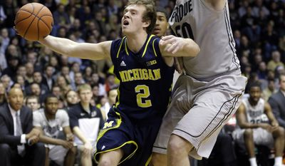 Michigan guard Spike Albrecht (2) attempts to drive under Purdue forward Travis Carroll in the first half of an NCAA college basketball game in West Lafayette, Ind., Wednesday, Feb. 26, 2014. (AP Photo/Michael Conroy)