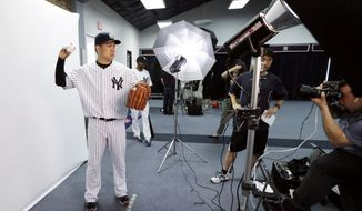 New York Yankees starting pitcher Masahiro Tanaka poses for a photographer during the Yankees' photo day before a spring training baseball practice Saturday, Feb. 22, 2014, in Tampa, Fla. (AP Photo/Charlie Neibergall)