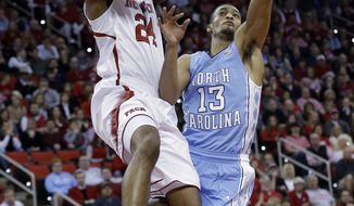 North Carolina's J.P. Tokoto (13) defends as North Carolina State's T.J. Warren (24) drives to the basket during the first half of an NCAA college basketball game in Raleigh, N.C., Wednesday, Feb. 26, 2014. (AP Photo/Gerry Broome)