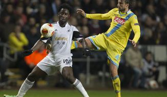 Swansea's Wilfried Bony, left, fights for the ball against Napoli's Henrique during their Europa League round of 32 first leg soccer match at the Liberty Stadium, Swansea, Wales, Thursday Feb. 20, 2014. (AP Photo/Jon Super)