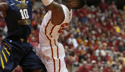 West Virginia guard Eron Harris tries to stop the shot of Iowa State guard DeAndre Kane during the first half of an NCAA college basketball game in Ames, Iowa, Wednesday, Feb. 26, 2014. (AP Photo/Justin Hayworth)