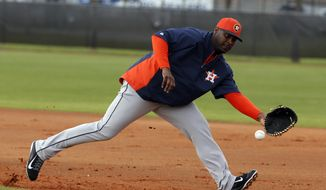 Houston Astros' Chris Carter fields a ground ball during a spring training baseball workout, Friday, Feb. 21, 2014, in Kissimmee, Fla. (AP Photo/Alex Brandon)
