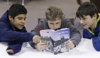 ADVANCE FOR USE SUNDAY, MARCH 2, 2014 AND THEREAFTER - In this Tuesday, Feb. 4, 2014 photo, from left, Erick Izquierdo, Josiah Spear, 12, and Cole McSorley, 12, look at a Trail Life handbook during a gathering of members in North Richland Hills, Texas. Trail Life USA says it has established units in more than 40 states, mostly from Boy Scouts and parents who feel the century-old organization has lost its way. (AP Photo/LM Otero)