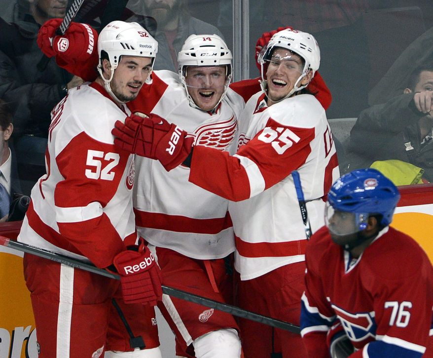 Detroit Red Wings center Gustav Nyquist (14) celebrates his winning goal with defensemen Jonathan Ericsson (52) and Danny DeKeyser (65) as Montreal Canadiens defenseman P.K. Subban (76) skates by during overtime in an NHL hockey game Wednesday, Feb. 26, 2014, in Montreal. Detroit won 2-1. (AP Photo/The Canadian Press, Ryan Remiorz)
