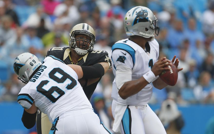 FILE - In this Sept. 16, 2012 file photo, Carolina Panthers left tackle Jordan Gross (69) keeps New Orleans Saints' Will Smith (91) blocked as Panthers quarterback Cam Newton (1) looks for a receiver during the first half of an NFL game in Charlotte, N.C. The Panthers will have to find someone new to protect Newton's blindside following the retirement of  Gross. (AP Photo/Bob Leverone, File)