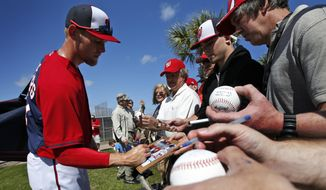 Washington Nationals starting pitcher Stephen Strasburg signs autographs after a spring training baseball workout, Thursday, Feb. 20, 2014, in VIera, Fla. (AP Photo/Alex Brandon)