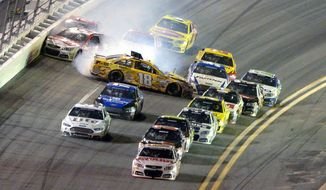 Dale Earnhardt Jr., front, leads the racers to the finish line as Kyle Busch (18) starts a collision coming out of Turn 4 during the NASCAR Daytona 500 auto race at Daytona International Speedway in Daytona Beach, Fla., Sunday, Feb. 23, 2014. (AP Photo/Phelan M. Ebenhack)