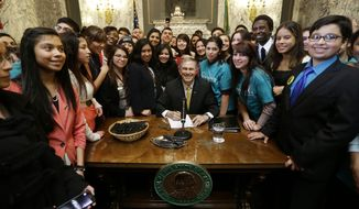 Washington Gov. Jay Inslee, center, poses for a photo with a group of students, after he signed into law a measure that expands state financial aid to students living illegally in the country, Wednesday, Feb. 26, 2014, at the Capitol in Olympia, Wash. (AP Photo/Ted S. Warren)