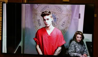 File-This Jan. 23, 2014, file photo shows Justin Bieber appearing in court via video feed in Miami. Video of Bieber at a South Florida police station after his January arrest is expected to be made public, with some sensitive parts omitted. Miami-Dade County prosecutors said DVDs of about 10 hours of video will be made public Wednesday, Feb. 26, 2014.  (AP Photo/The Miami Herald, Walter Michot, File)