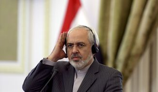 Iranian Foreign Minister Mohammad Javad Zarif holds his earphone on his ear while listening to the translation of a question in a joint press conference with his Iraqi counterpart Hoshyar Zebari, in Tehran, Iran, Wednesday, Feb. 26, 2014. (AP Photo/Vahid Salemi)