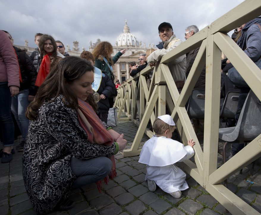 Paola Ciabattini looks at her 19-month-old son Daniele De Sanctis, dressed up as a pope, during Pope Francis' weekly general audience in St. Peter's Square at the Vatican, Wednesday, Feb. 26, 2014. Francis kissed the child as the new must-have Carnival costume made its debut at the pope's general audience Wednesday. Daniele, who was crying, was hoisted up to Francis as he drove by in his open-topped jeep. During Carnival in Italy, children often go to school and spend their weekends dressed up in pirate, princess — and now pope — costumes. Carnival, also known as mardi gras, marks the period before the church's solemn Lenten season begins. Ciabattini said she dressed her son as a pope in a demonstration of affection towards Pope Francis. (AP Photo/Alessandra Tarantino)