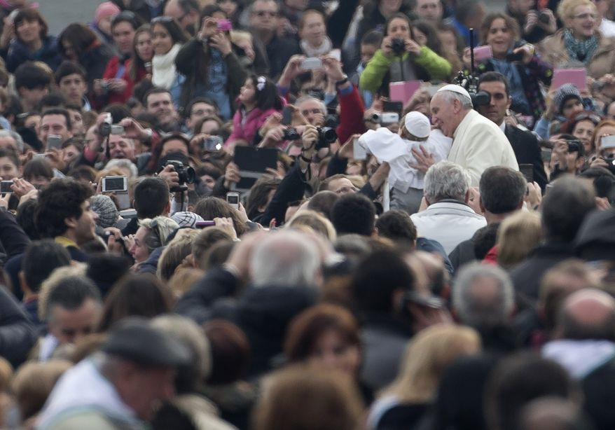 A child, Daniele, no last name available, dressed as a pope is held up to Pope Francis as the pontiff is driven through the crowd upon his arrival for his weekly general audience in St. Peter's Square at the Vatican, Wednesday, Feb. 26, 2014. The child, who was crying, was hoisted up to Francis as he drove by in his open-topped jeep. Another child dressed in a similar white cassock and white skullcap was also on hand as were kids dressed as Swiss Guards. During Carnival in Italy, children often go to school and spend their weekends dressed up in pirate, princess — and now pope — costumes. Carnival, also known as mardi gras, marks the period before the church's solemn Lenten season begins.  (AP Photo/Alessandra Tarantino)