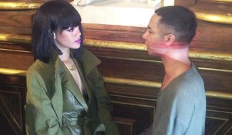Singer Rihanna holds hands with Balmain fashion designer Olivier Rousteing after Balmain's ready-to-wear fall/winter 2014-2015 fashion collection presented in Paris, Thursday, Feb. 27, 2014. (AP Photo/Thomas Adamson)