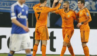 Real's Cristiano Ronaldo, Real's Karim Benzema and Real's Gareth Bale, from left, celebrate their team's fourth goal during the Champions League round of the last 16 first leg soccer match between Schalke 04 and Real Madrid in Gelsenkirchen, Germany, Wednesday, Feb.26,2014. (AP Photo/Frank Augstein)