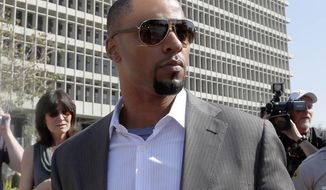 In this Feb. 14, 2014, photo, former NFL safety Darren Sharper leaves a courthouse in Los Angeles. An arrest warrant has been issued for Sharper and another man, accusing them of raping two women in New Orleans last year. Sharper also is under investigation in sexual assault cases in Florida, Nevada and Arizona and has pleaded not guilty to rape charges in Los Angeles. (AP Photo/Nick Ut )