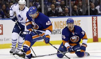 New York Islanders' Cal Clutterbuck (15) passes the puck to teammate Michael Grabner (40) as Toronto Maple Leafs' Jake Gardiner (51) watches during the second period of an NHL hockey game Thursday, Feb. 27, 2014, in Uniondale, N.Y. (AP Photo/Frank Franklin II)